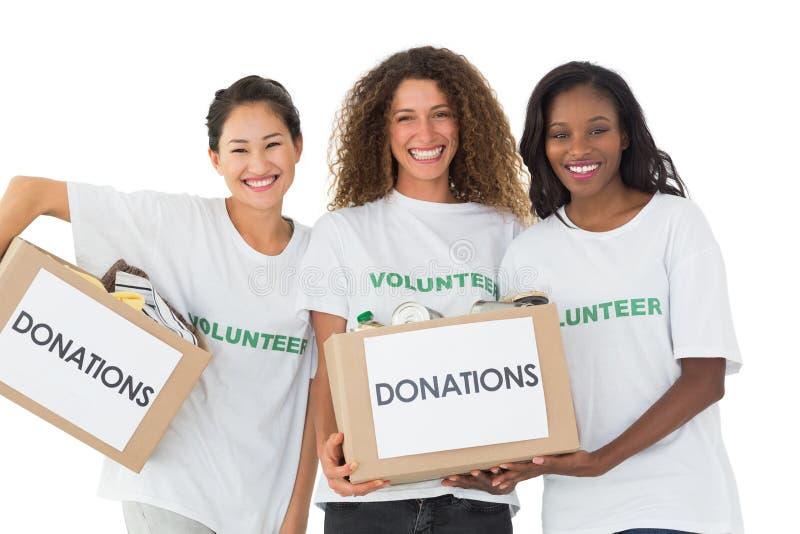 Счастливая команда волонтеров усмехаясь на камере держа коробки пожертвований стоковое изображение