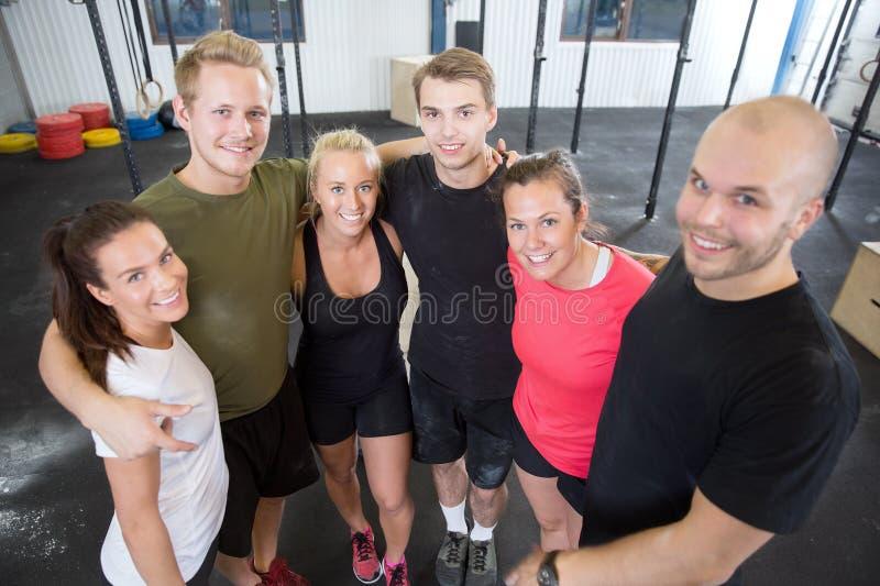 Счастливая команда разминки фитнеса на спортзале стоковое фото rf