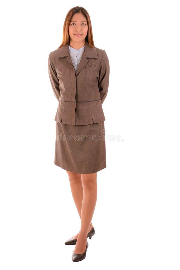 Счастливая коммерсантка в коричневом костюме стоящ и усмехающся на whi стоковая фотография