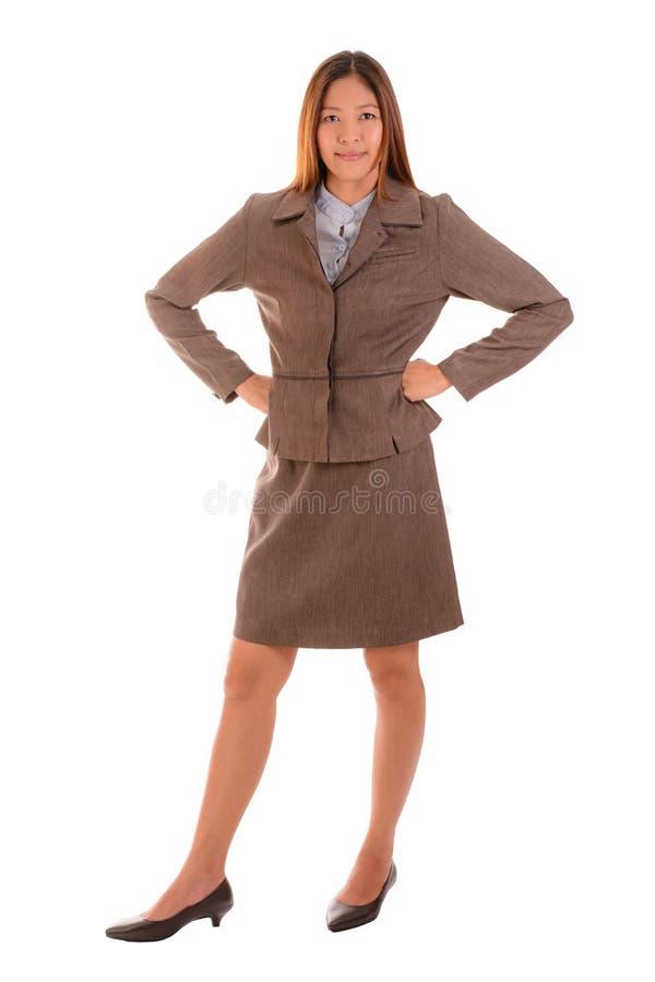 Счастливая коммерсантка в коричневом костюме усмехается и подготовляет подбоченясь дальше стоковая фотография