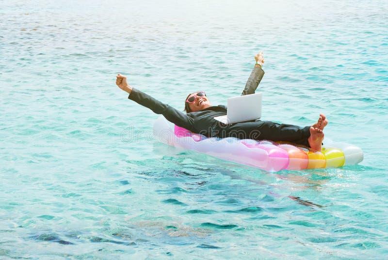 Счастливая коммерсантка отдыхая на lilo с компьтер-книжкой стоковое изображение rf