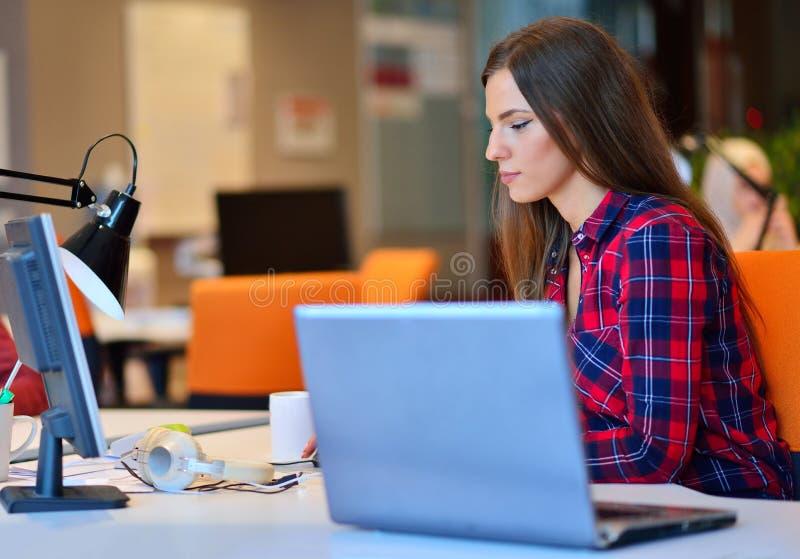 Счастливая коммерсантка работая на ее компьтер-книжке в офисе стоковые фотографии rf