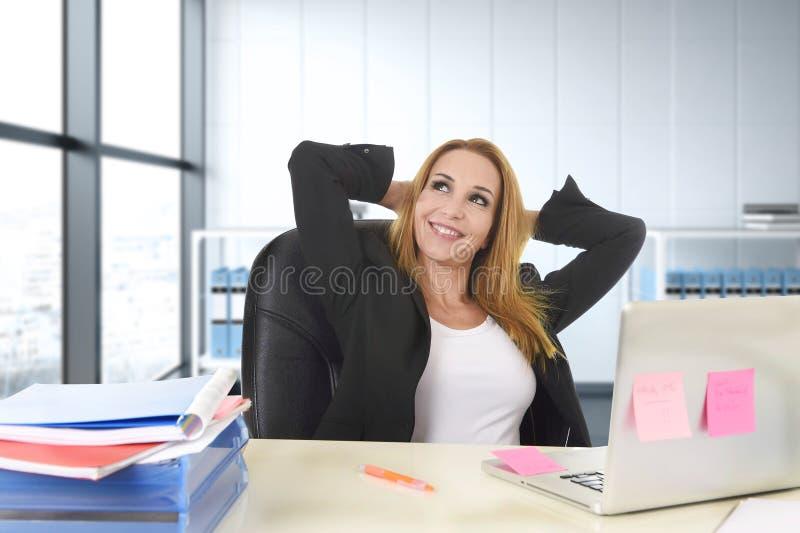 Счастливая коммерсантка работая на портативном компьютере офиса сидя на столе ослабила стоковая фотография rf