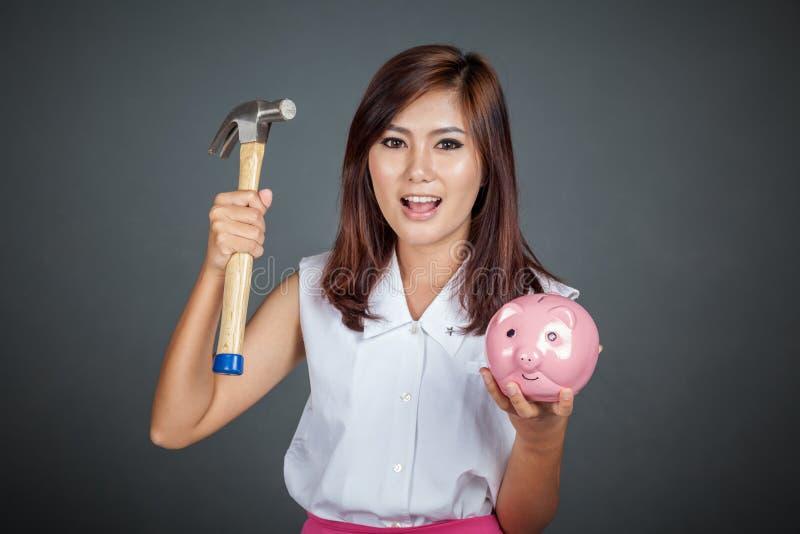 Счастливая красивая азиатская девушка с розовыми денежным ящиком и молотком свиньи стоковые фото