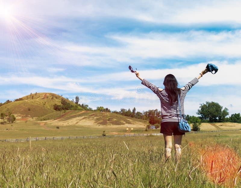Счастливая красивая азиатская женщина с шляпой и сумка готовая для того чтобы начать каникулы на угле с горой пейзажа в предпосыл стоковые фото