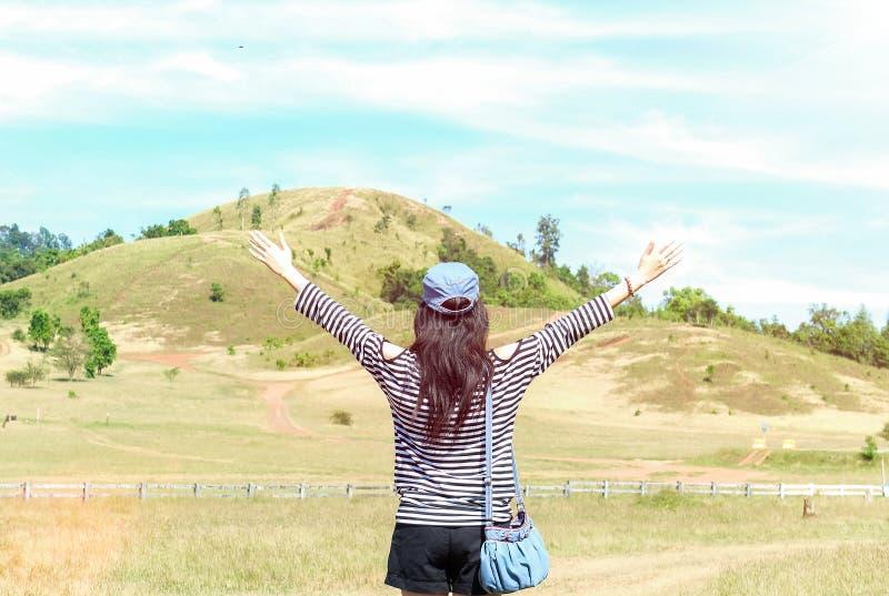 Счастливая красивая азиатская женщина с шляпой и сумкой протягивала ее оружия готовые для того чтобы начать каникулы с горой пейз стоковые изображения rf