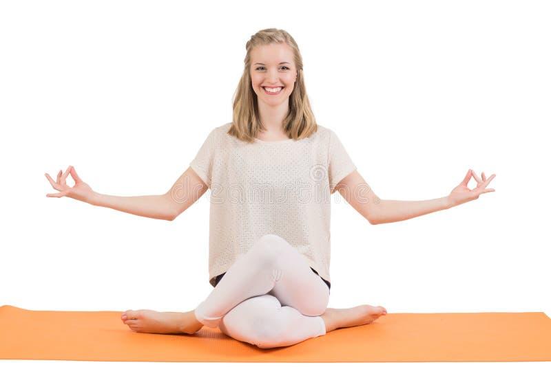 Счастливая красивая белокурая женщина делая йогу на циновке стоковое фото
