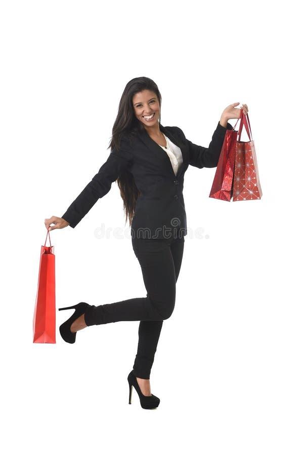 Счастливая красивая женщина в элегантном костюме держа хозяйственные сумки продажи возбудила жизнерадостное стоковая фотография