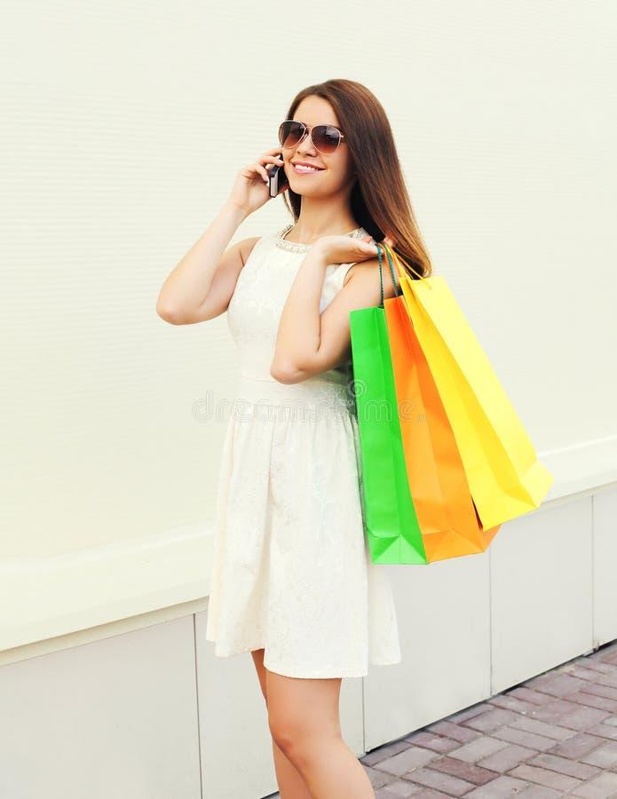 Счастливая красивая молодая усмехаясь женщина с ходя по магазинам красочными сумками стоковые изображения rf
