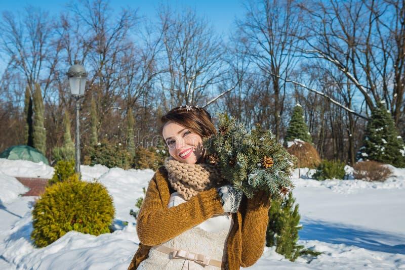 Счастливая красивая невеста в снежном зимнем дне солнечная погода стильно с букетом свадьбы сделанным от сосны ручной работы mitt стоковая фотография rf
