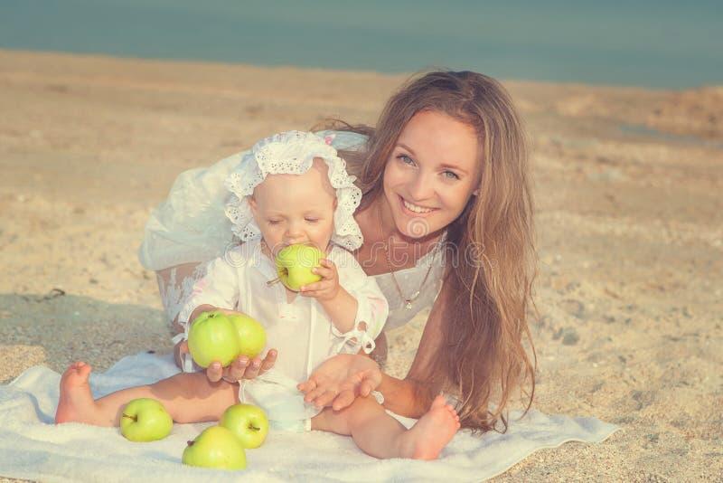 Счастливая красивые мать и дочь наслаждаясь временем пляжа стоковые фото