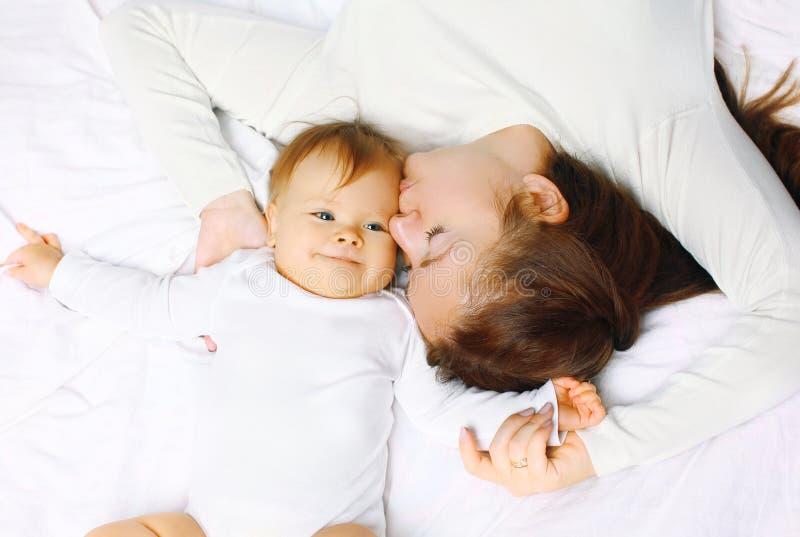 Счастливая мать и младенец лежа на кровати дома стоковое изображение