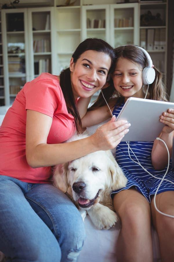 Счастливая мать и дочь сидя с собакой и слушая к музыке на наушниках стоковые изображения rf