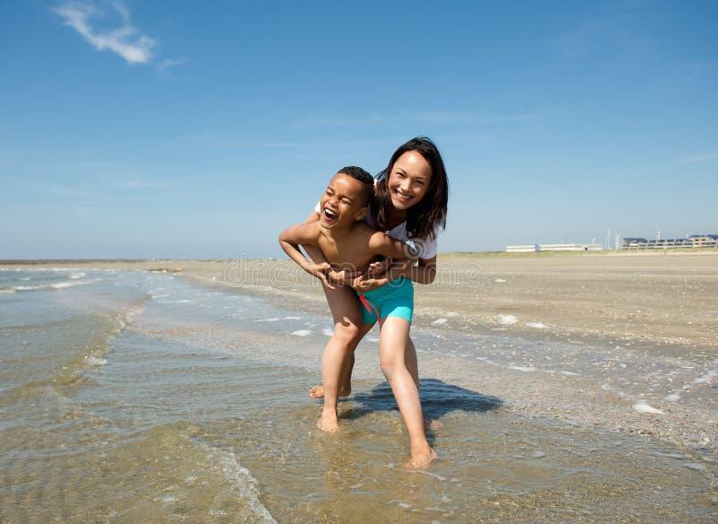 Download Счастливая мать и сын играя на пляже Стоковое Изображение - изображение насчитывающей наслаждаться, актеров: 41653447