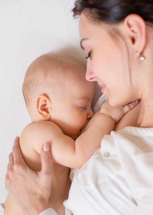 Счастливая мать кормя ее младенца грудью младенца стоковые изображения rf