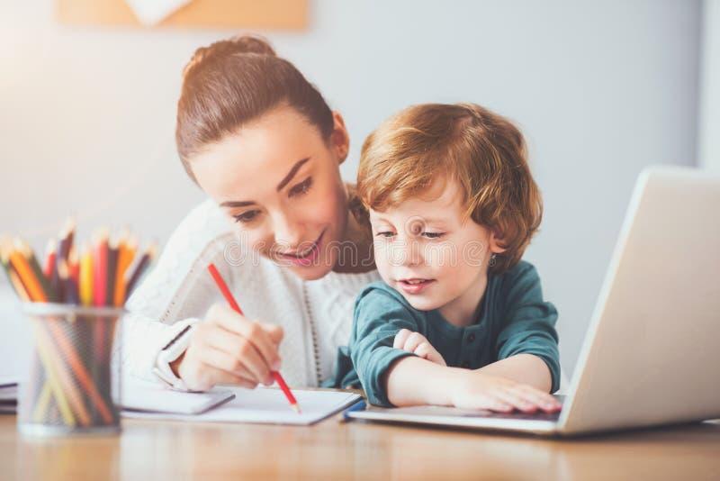 Счастливая мать показывая ее сыну как написать стоковая фотография rf