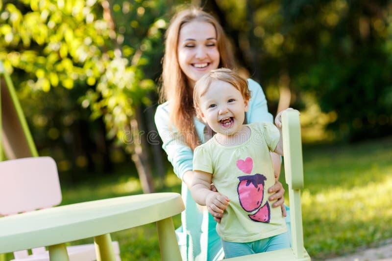 Счастливая мать при дочь сидя на children& x27; стул s стоковое фото