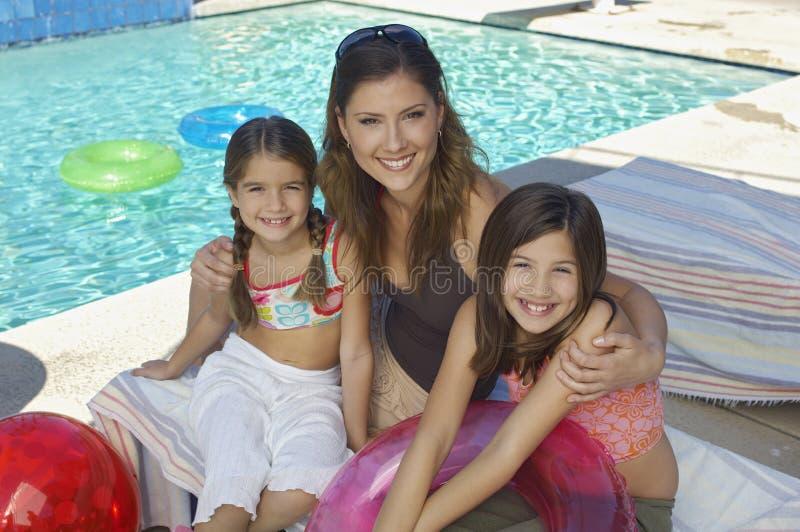 Счастливая мать сидя с дочерьми стоковая фотография