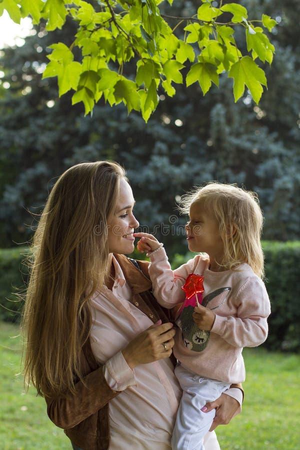 Счастливая мать с девушкой потакает в парке стоковая фотография