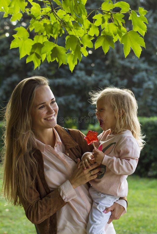 Счастливая мать с девушкой потакает в парке стоковое изображение rf