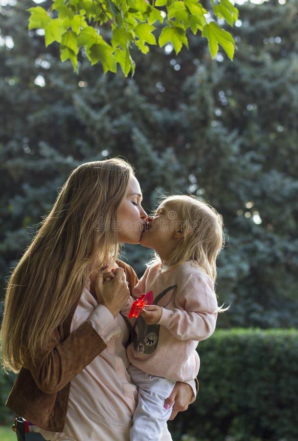 Счастливая мать с ее ребёнком потакает стоковое фото