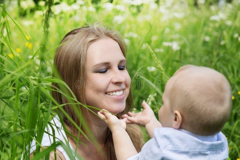 Счастливая мать с ее сыном в луге стоковые фотографии rf