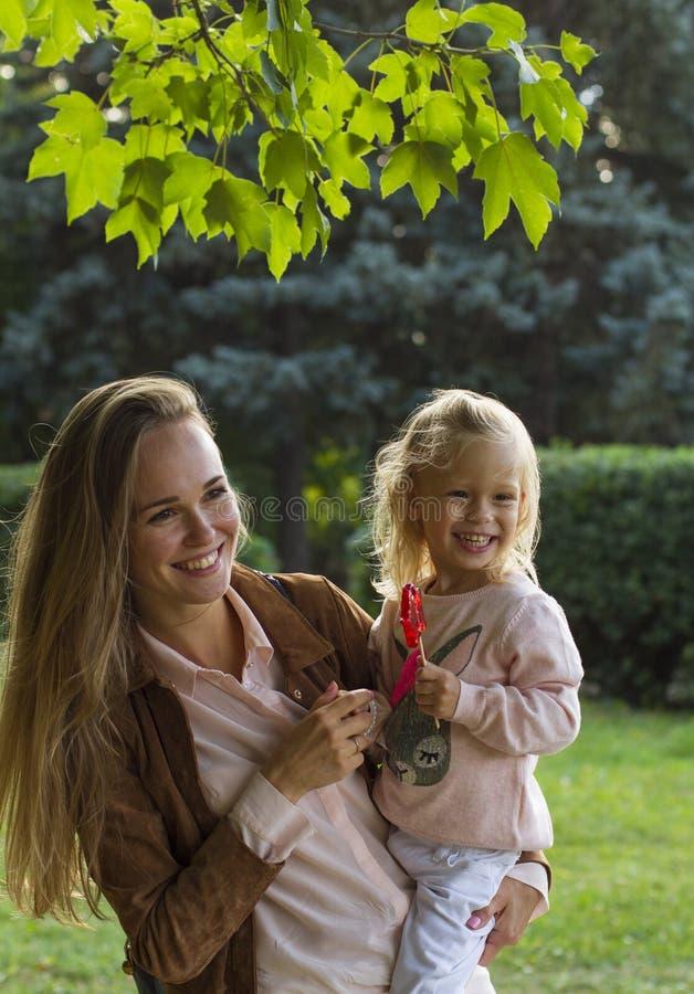Счастливая мать с ребёнком в парке стоковые изображения