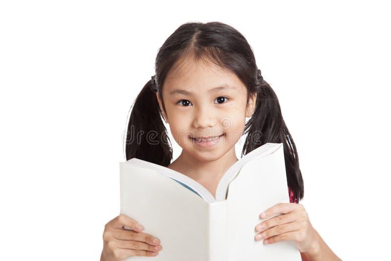 Счастливая маленькая азиатская девушка прочитала книгу стоковое фото