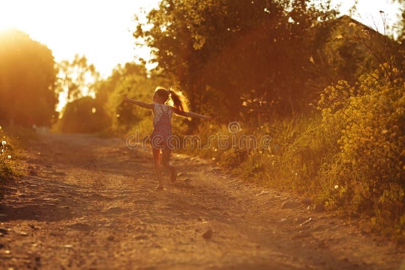 Счастливая маленькая девочка бежать вдоль проселочной дороги стоковые фото