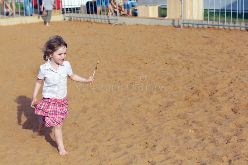 Счастливая маленькая девочка бежит с ярким леденцом на палочке на песке стоковая фотография rf