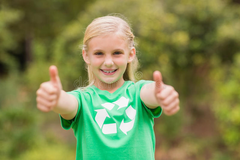 Счастливая маленькая девочка в зеленом цвете с большими пальцами руки вверх стоковое изображение