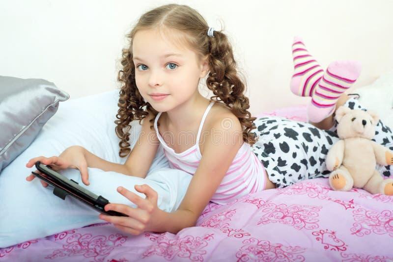 Счастливая маленькая девочка лежа на кровати с планшетом стоковое изображение