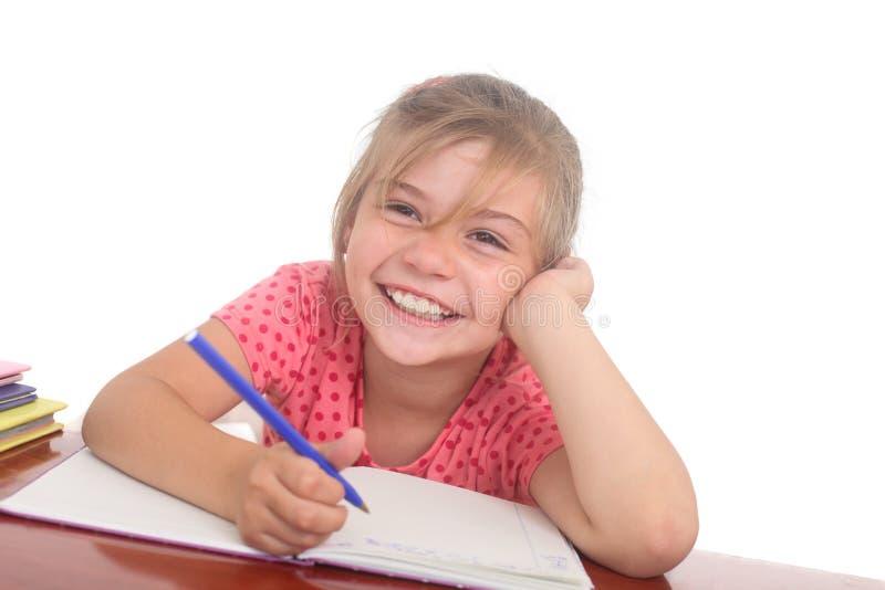 Счастливая маленькая девочка делая домашнюю работу стоковые изображения rf