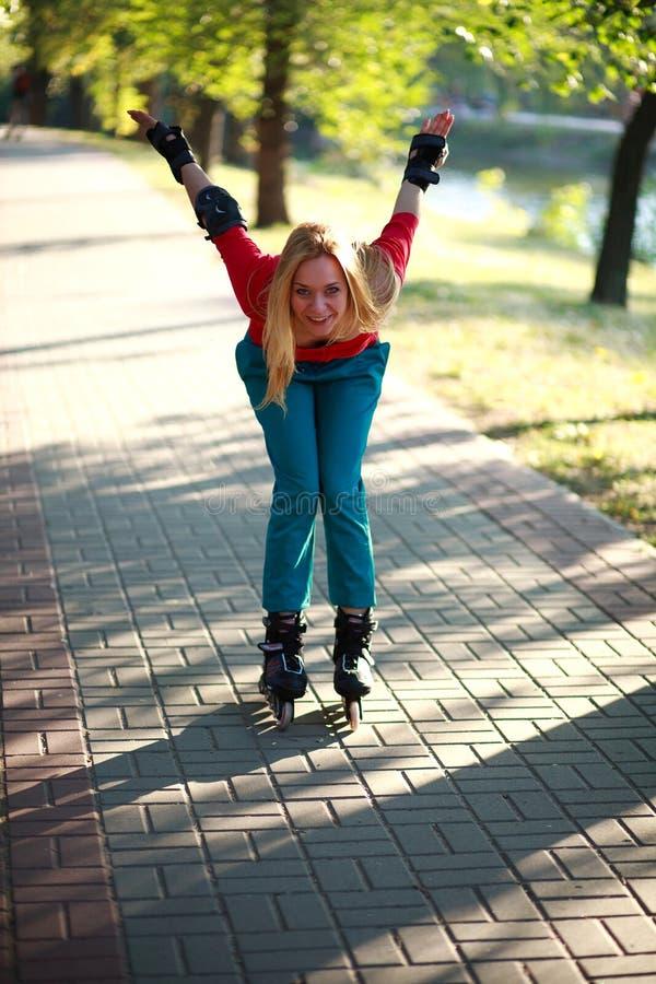 Счастливая маленькая девочка наслаждаясь кататься на коньках ролика в парке стоковые фотографии rf