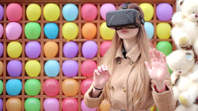 Счастливая маленькая девочка на улице в бежевом пальто играя имеющ стекла виртуальной реальности vr потехи нося, красочную предпо сток-видео