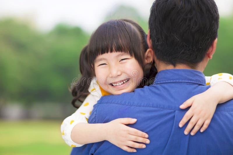 Счастливая маленькая девочка обнимая обнимающ ее отца стоковые изображения