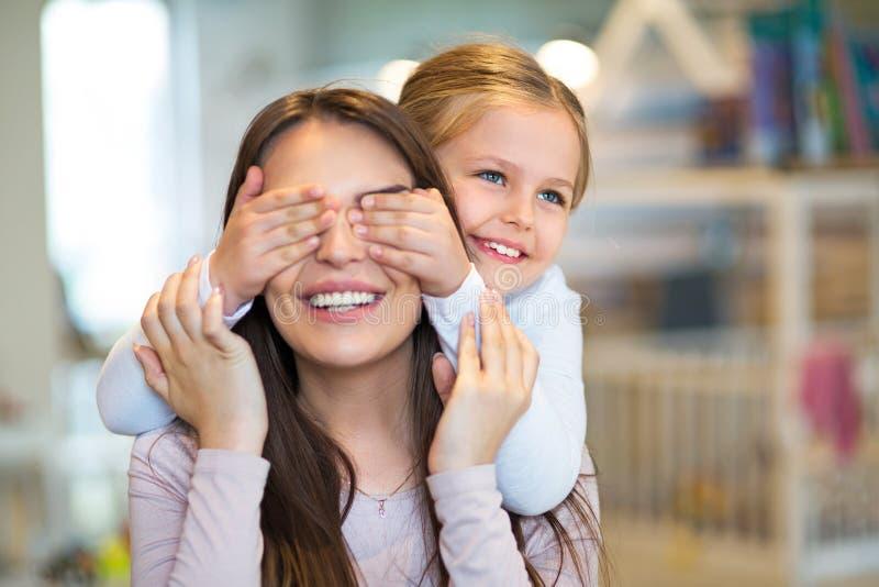 Счастливая маленькая девочка покрывает ее глаза матери стоковая фотография rf