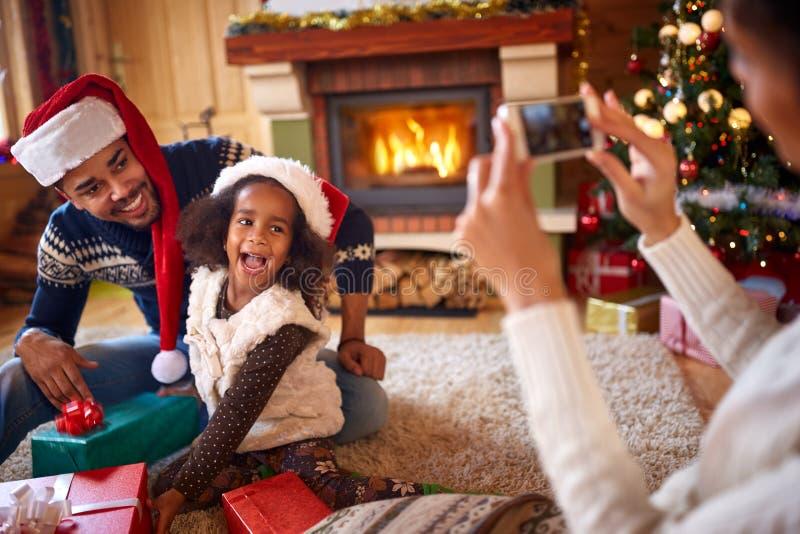 Счастливая маленькая девочка представляя ее маму для фото рождества стоковое фото
