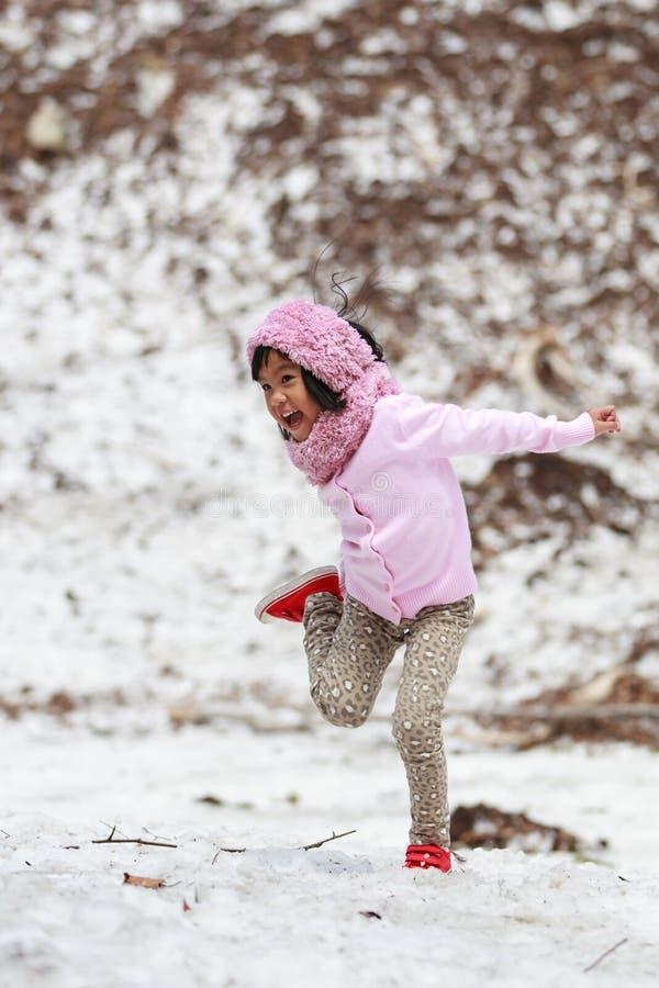 Счастливая маленькая девочка скача на снег стоковая фотография rf