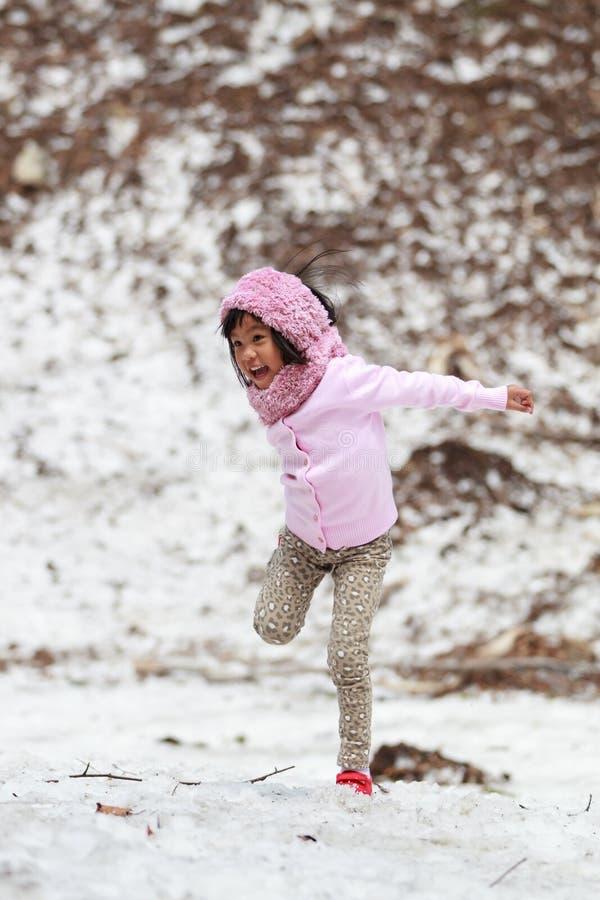 Счастливая маленькая девочка скача на снег стоковые фотографии rf