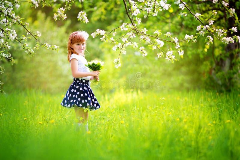 Счастливая маленькая девочка с букетом лилий долины имея стоковая фотография rf