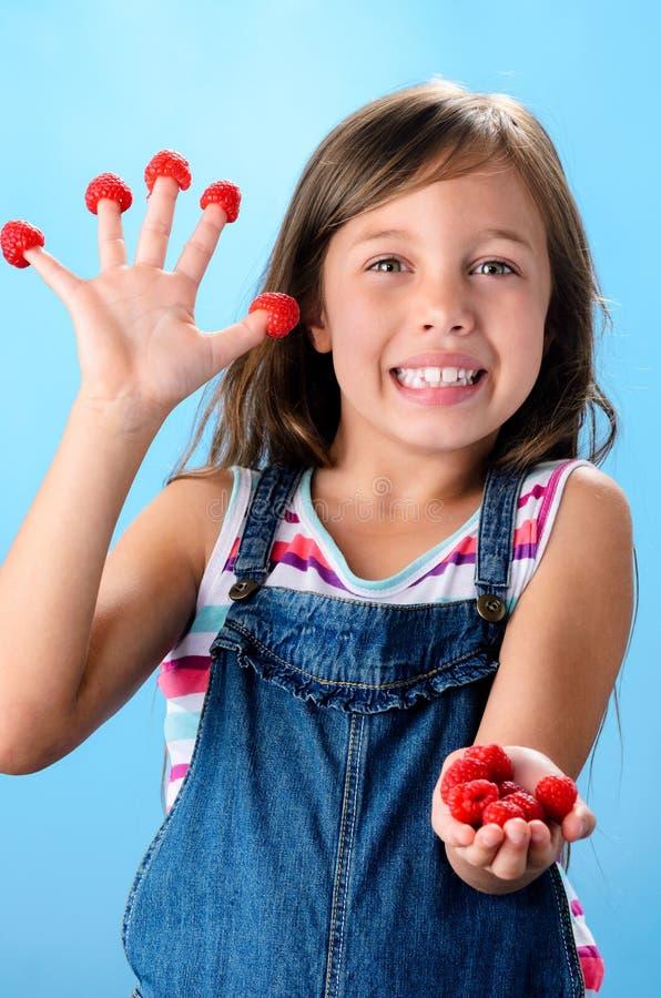 Счастливая маленькая девочка с rapsberry стоковые фото
