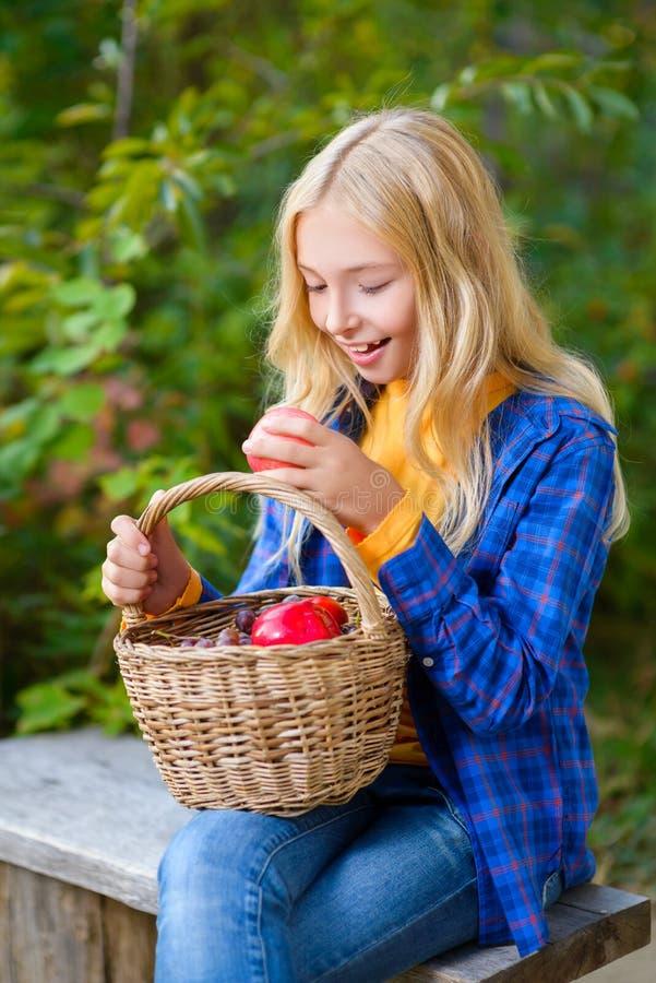Счастливая маленькая девочка усмехаясь держащ яблока в стоковое фото