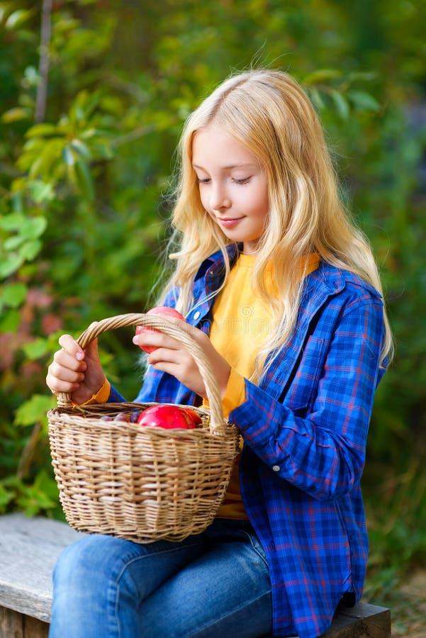 Счастливая маленькая девочка усмехаясь держащ яблока в стоковое изображение