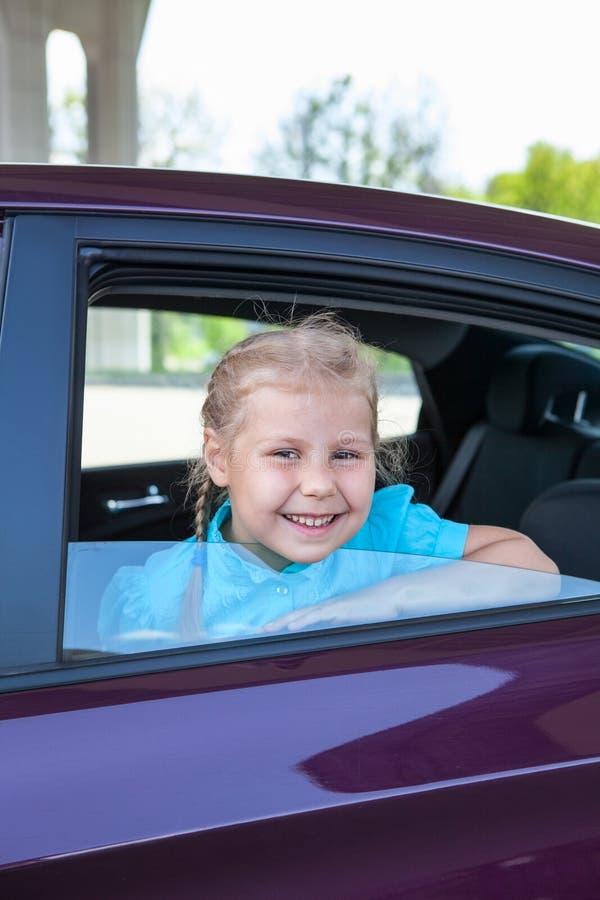 Счастливая маленькая девочка усмехаясь от окна автомобиля стоковые фотографии rf