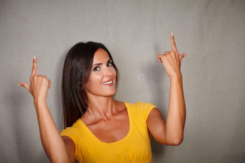 Счастливая малолетка указывая вверх пока усмехающся стоковая фотография