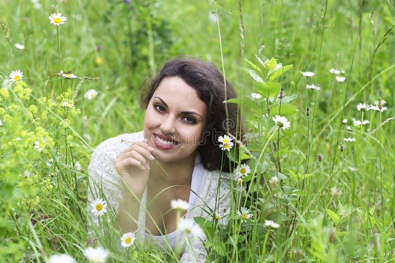 Счастливая милая женщина брюнет в поле стоцвета стоковые фото