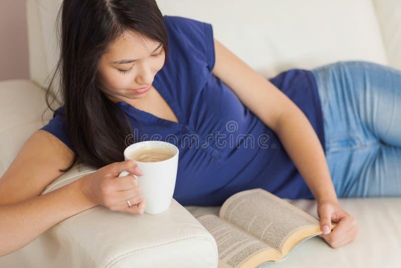 Счастливая молодая азиатская женщина лежа на софе читая удерживание книги стоковое фото