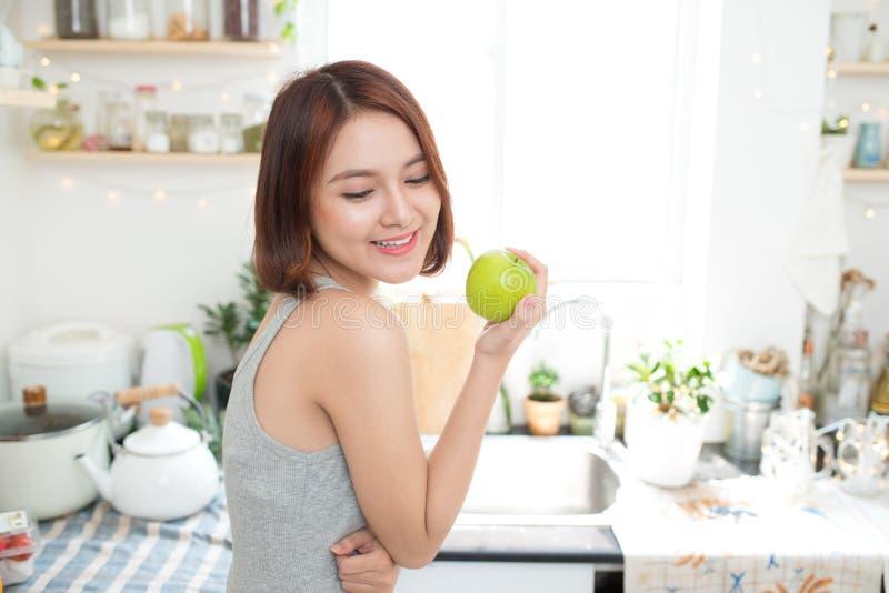 Счастливая молодая азиатская женщина есть зеленое Яблоко на кухне Диета умрите стоковые изображения
