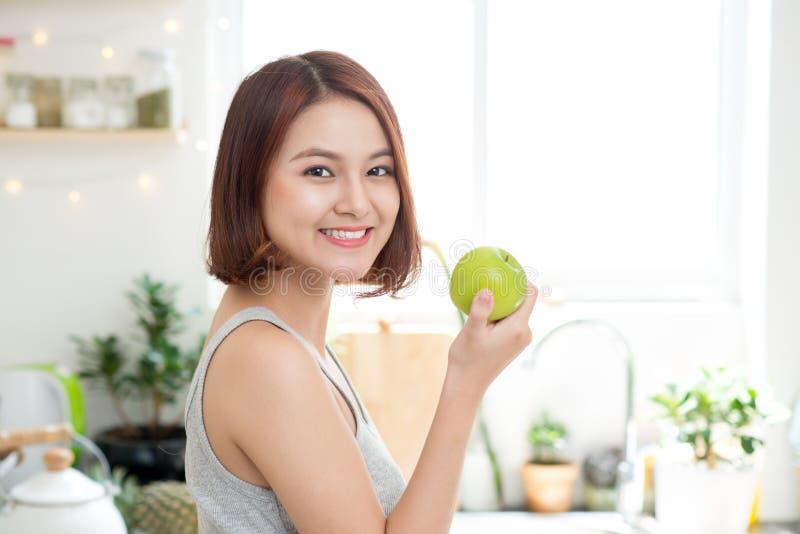 Счастливая молодая азиатская женщина есть зеленое Яблоко на кухне Диета умрите стоковое изображение